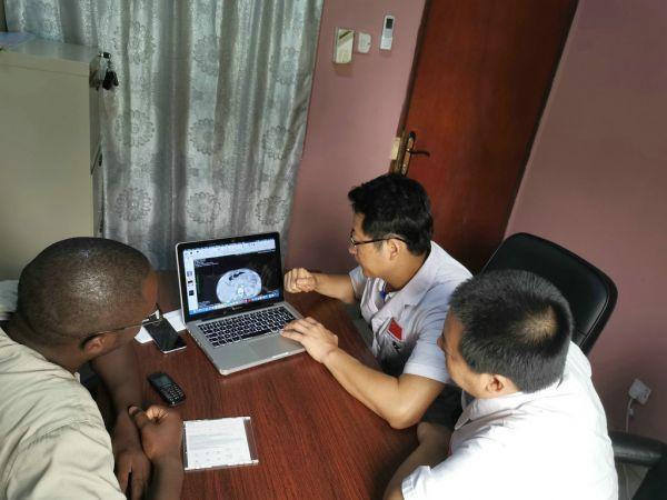 1.中国(辽宁)第三批援冈比亚医疗队队长梁松年会同当地医护为患者会诊