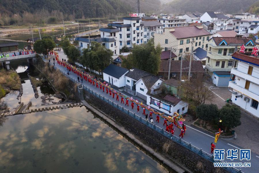 2月23日,百米长的板龙在湖源乡窈口村内踩街(无人机照片)。新华社记者 徐昱 摄11