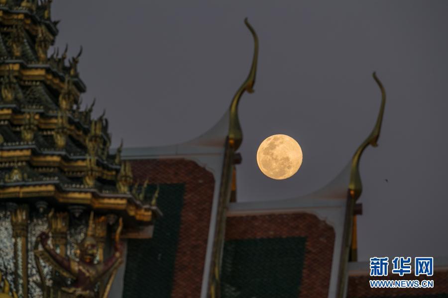 2月26日,一轮圆月从泰国曼谷大王宫建筑群背后升起。新华社记者 张可任 摄