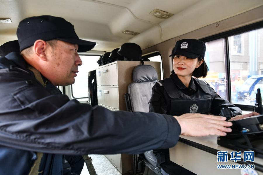 师傅黄厚杰在巡逻车上向王潇(右)传授经验(3月4日摄)。