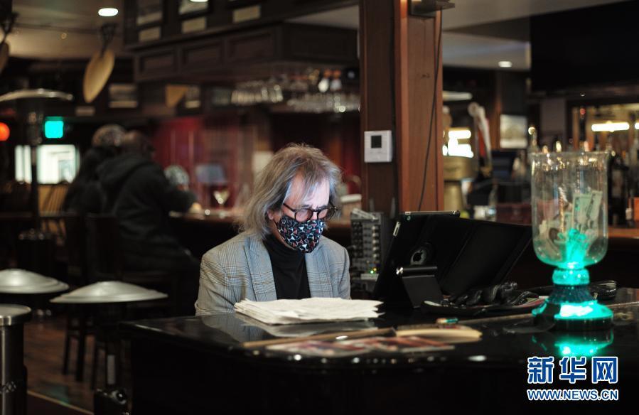 """3月5日,一名钢琴师在美国加利福尼亚州半月湾市一家餐馆内为顾客演奏。半月湾所在的圣马特奥县目前已从加州四级防疫层级中最高的""""紫色""""等级进入""""红色""""等级。餐馆可以恢复堂食。电影院、博物馆和健身房等室内活动在控制客流的前提下重新开放,并放宽了人员在室外活动的时间限制。新华社记者 吴晓凌 摄"""