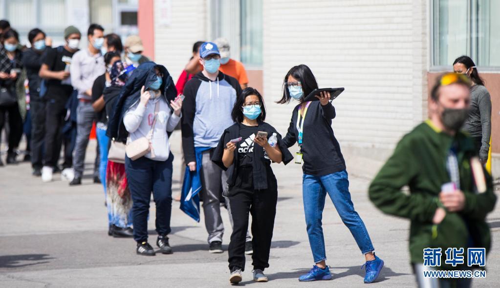 4月10日,在加拿大多伦多一个临时疫苗接种点,人们排队等待接种新冠疫苗。据加拿大电视台报道,截至当地时间10日下午,加拿大累计新冠确诊病例超过105万例,达1051246例,累计死亡病例23282例。新华社发(邹峥摄)