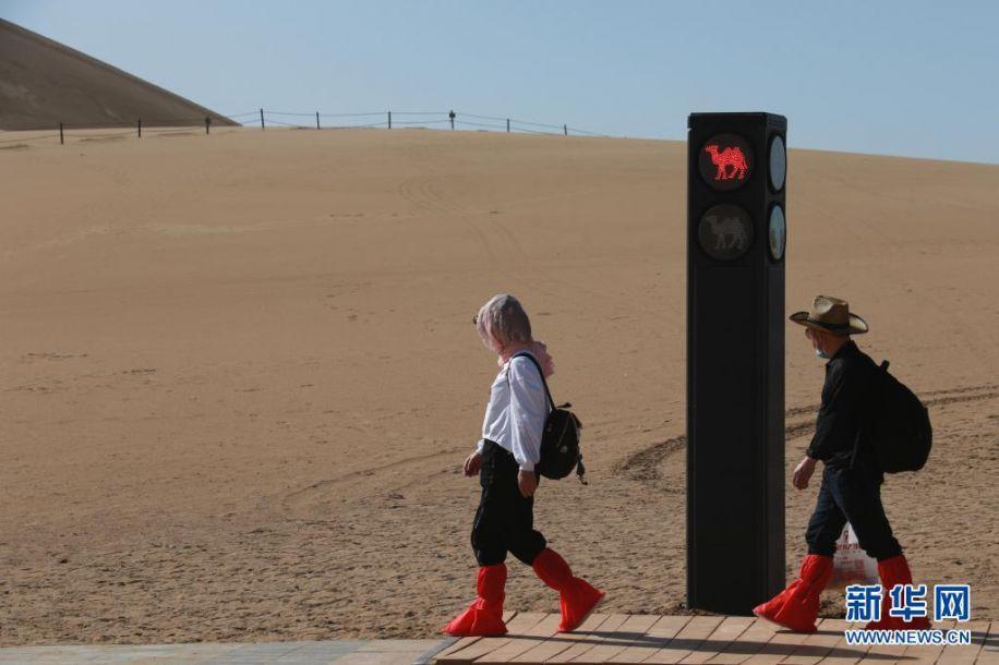 """4月11日,敦煌市鸣沙山月牙泉景区的交通信号灯""""行人绿灯""""亮时,游客从步行道上有序通过。近日,具有骆驼元素的交通信号灯亮相甘肃省敦煌市鸣沙山月牙泉景区。针对景区内骆驼行走的路线、游人步行道和车辆行驶道交叉的情况,鸣沙山月牙泉景区设计出引导人、车和骆驼分流用的交通信号灯,确保景区交通安全有序。新华社发(张晓亮 摄)5"""
