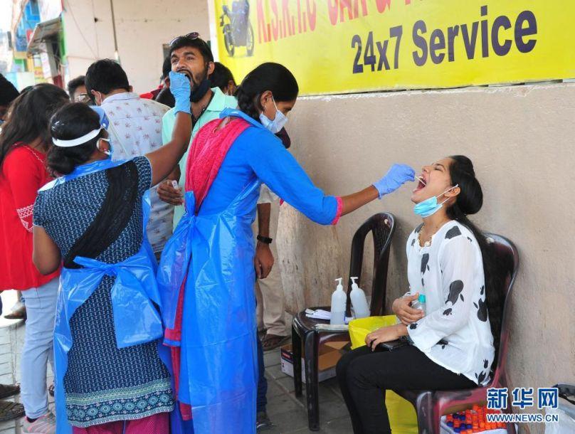 4月11日,人们在印度班加罗尔的一个公交站接受新冠病毒检测取样。印度卫生部11日公布的数据显示,印度单日新增新冠确诊病例152879例,再创疫情以来新高,累计确诊13358805例;新增死亡839例,累计死亡169275例。新华社发2