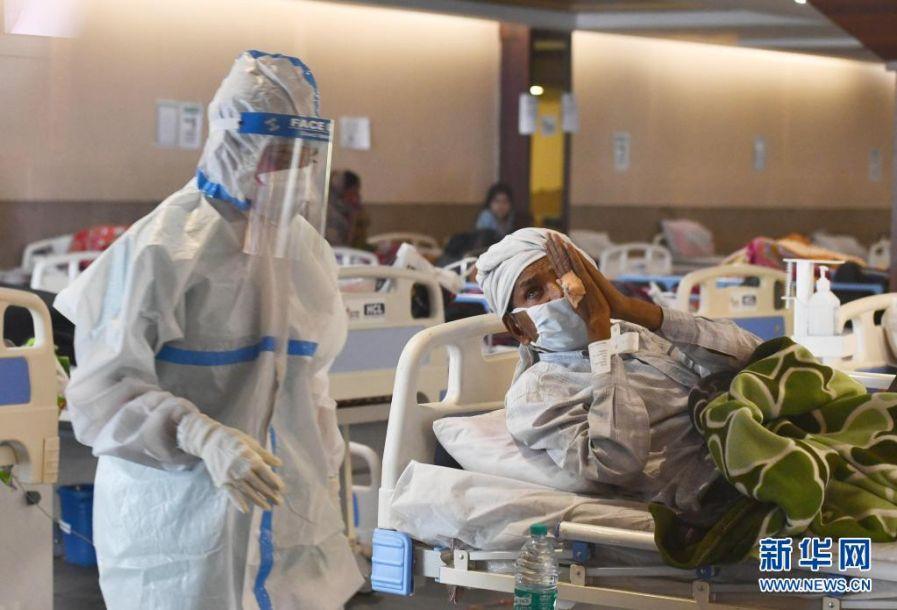 4月13日,医务人员身着防护服在印度首都新德里一家医院的隔离区照看新冠病人。世界卫生组织最新发布的全球新冠疫情周报显示,截至4月11日的一周内,全球新增新冠确诊病例约450万例。其中印度一周新增确诊数居全球首位,超过87万例,比前一周增加70%。新华社发(帕塔·萨卡尔摄)