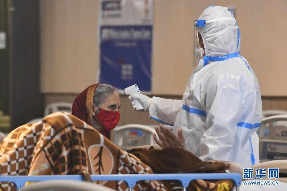 4月13日,医务人员身着防护服在印度首都新德里一家医院的隔离区照看新冠病人。世界卫生组织最新发布的全球新冠疫情周报显示,截至4月11日的一周内,全球新增新冠确诊病例约450万例。其中印度一周新增确诊数居全球首位,超过87万例,比前一周增加70%。新华社发(帕塔·萨卡尔摄)5