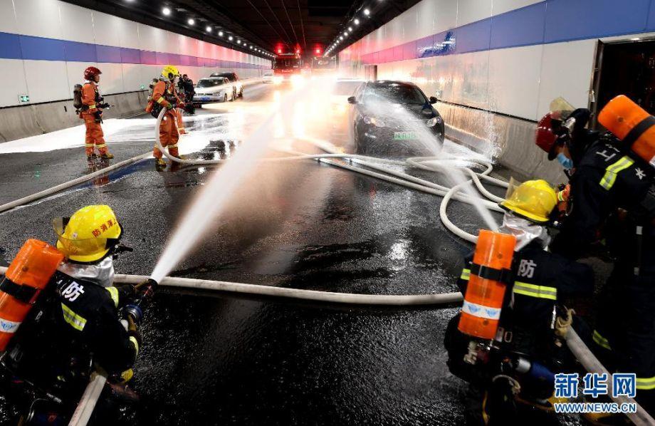 """4月21日,参加演练的消防员对发生碰撞失火的车辆实施灭火。当日凌晨,为应对即将到来的""""五一""""长假车流高峰,上海市长宁区消防救援支队在上海北翟路隧道举行灭火救援演练。演练模拟隧道内发生车辆火灾事故,交通、消防、公安、卫生等部门迅速启动联动救援机制,救援、灭火、疏散等程序有序展开,检验了隧道火灾事故的应急处置和协同作战能力。新华社记者 陈飞 摄"""
