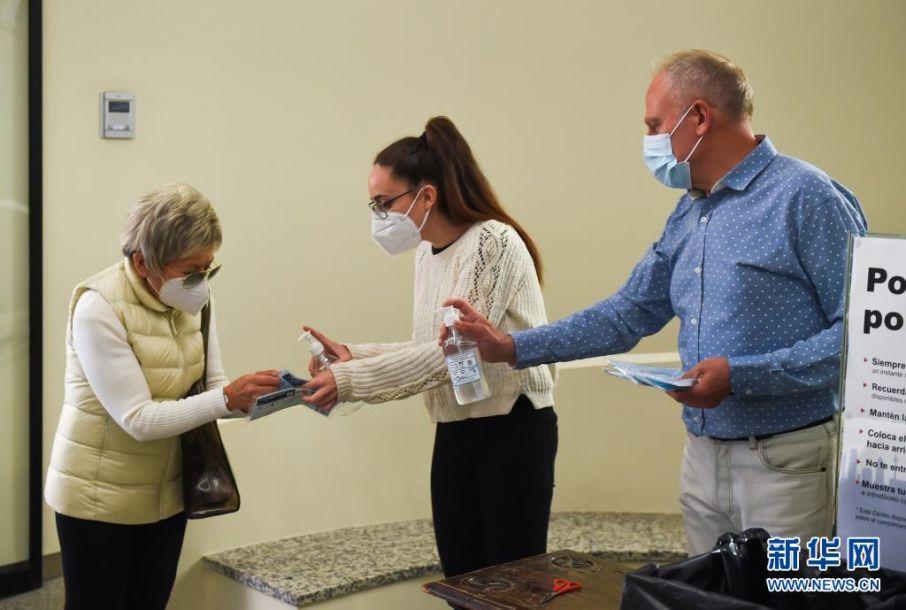 5月4日,工作人员在西班牙马德里一处投票点为选民消毒。当日,马德里自治区举行选举,西班牙人民党候选人、现任马德里自治区主席阿尤索成功连任。新华社发(古斯塔沃·巴连特摄)