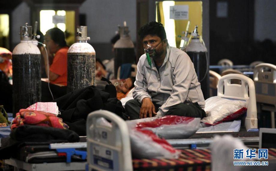5月8日,新冠患者在印度新德里的一处隔离中心吸氧。据印度卫生部8日公布的数据,该国较前一日新增新冠死亡病例4187例,为疫情暴发以来首次突破4000例。截至当天,印度单日新增新冠确诊病例数已连续3天超过40万例,连续17天超过30万例。新华社发(帕塔·萨卡尔 摄)