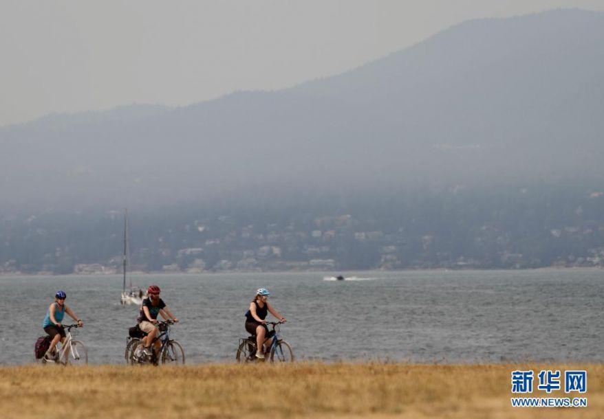 8月1日,多名骑车游客从烟雾笼罩的温哥华郊区驶过。新华社发(梁森摄)