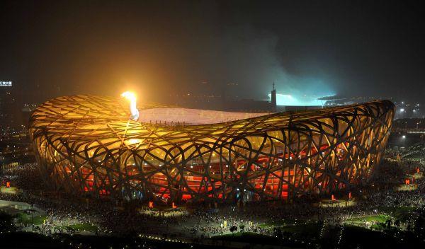 """2008年8月8日,奥运圣火在国家体育场——""""鸟巢""""熊熊燃烧。(新华社)"""