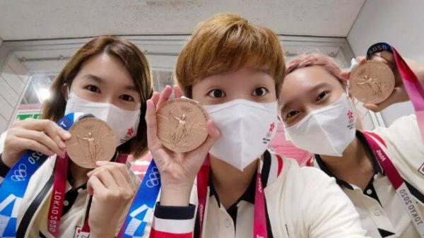 杜凯琹(中)和队友们与奥运奖牌合影。(新华社客户端,受访者供图)