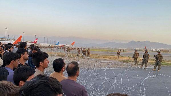 8月16日,在阿富汗喀布尔机场,美军士兵用隔离带挡住阿富汗民众。新华社/法新