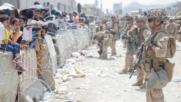 8月20日,美军士兵与阿富汗民众站在阿富汗喀布尔机场的铁丝网隔离带两侧。新华社/路透
