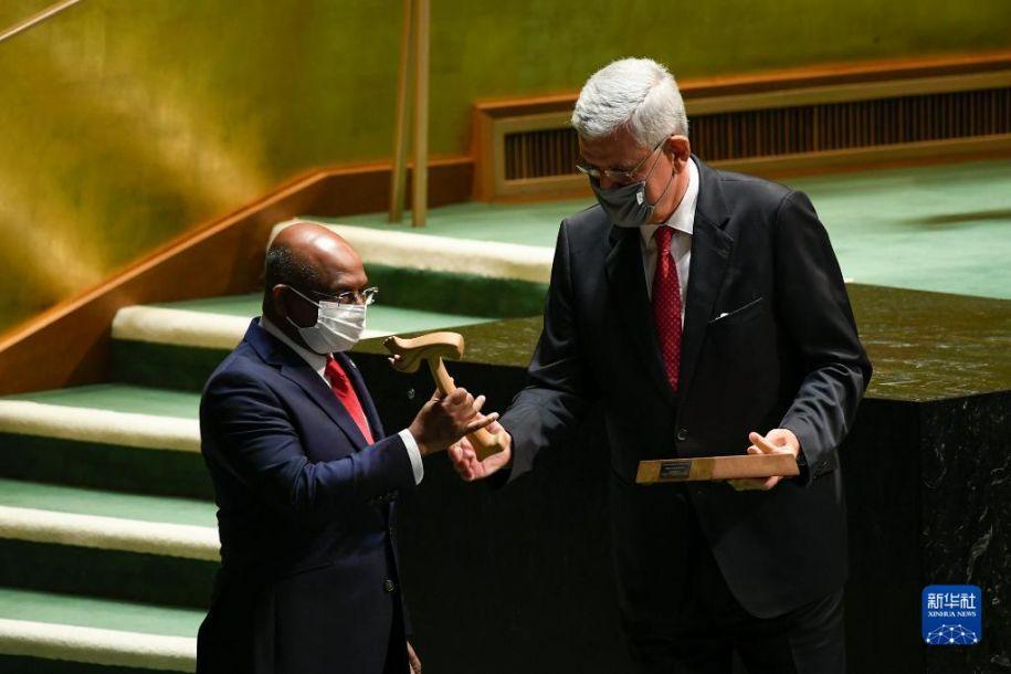9月14日,在位于纽约的联合国总部,第76届联合国大会主席阿卜杜拉·沙希德(左)从上届联大主席博兹克尔手中接过象征联大主席权力的木槌。第76届联合国大会14日在纽约联合国总部开幕。新华社发(联合国供图/埃万·施奈德摄)