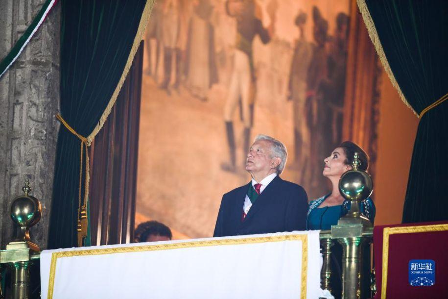 9月15日,墨西哥总统洛佩斯(左)和夫人在首都墨西哥城中心的国家宫出席独立日庆祝活动时挥手致意。当日,墨西哥举行独立日庆祝活动。新华社记者 辛悦卫 摄