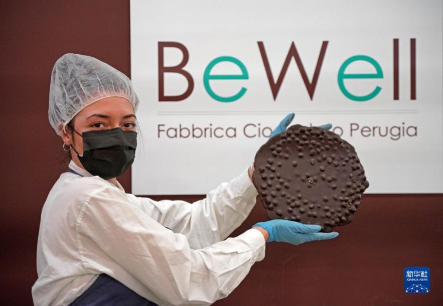 """10月15日,一名女子在意大利佩鲁贾""""欧洲巧克力节""""上展示一块巧克力。新华社记者金马梦妮摄"""